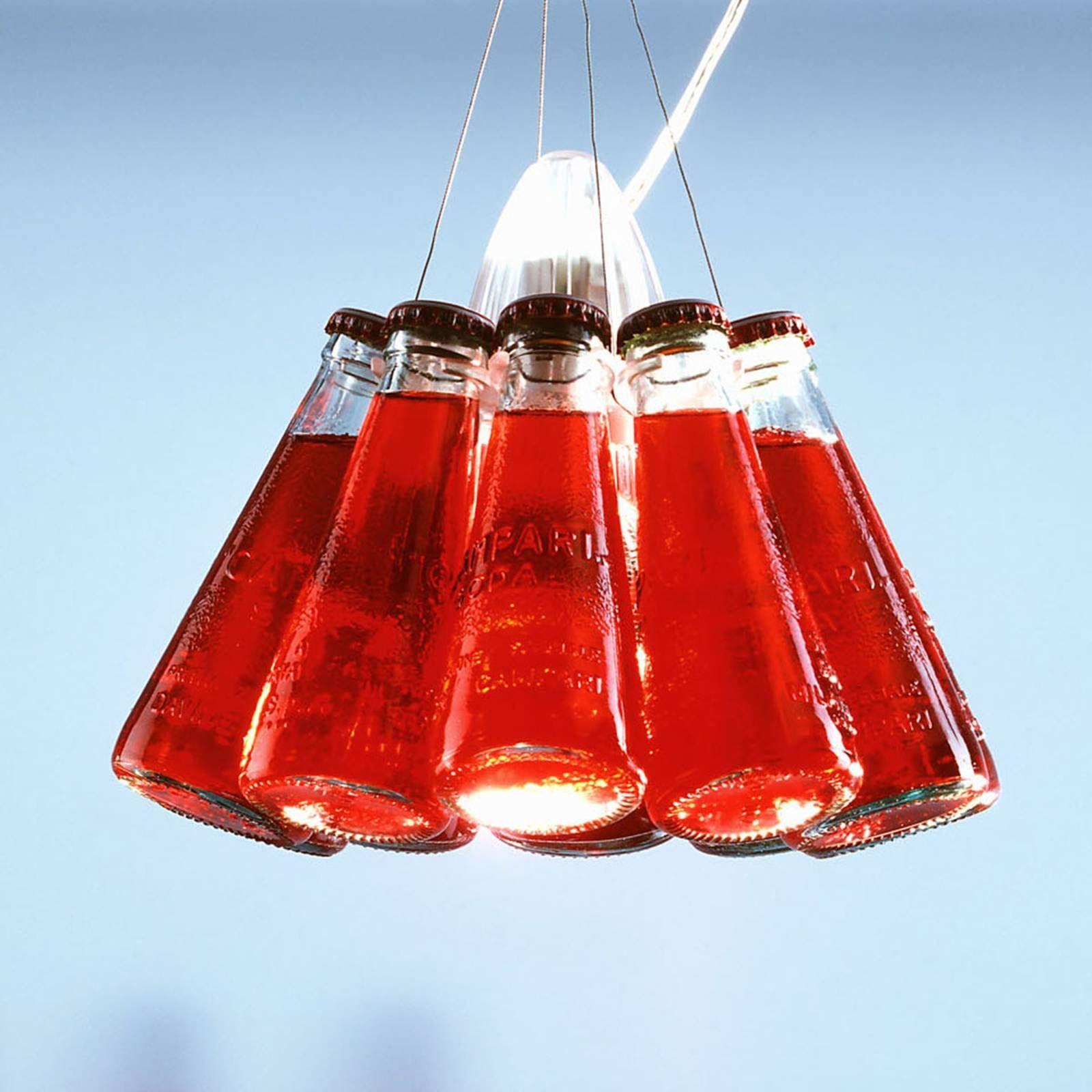 Campari Light: lámpara colgante de diseño con diez botellas de Campari Soda auténticas La lámpara colgante Campari Light de Ingo Maurer constituye ¡el atractivo de cualquier coctelería! Para su creación no se han limitado a rellenar botellas de vidrio simplemente con agua con colorante rojo y a servirlas como una Campari. Ni por asomo. Se trata de diez botellas Campari Soda originales que, en su conjunto, conforman la sensacional lámpara colgante Campari Light. En el centro de las botellas dispu