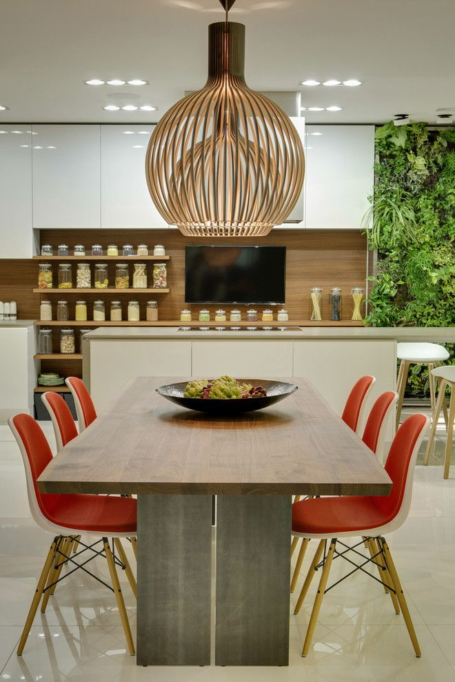Long wooden dining table paired with a set of brightly coloured modern chairs in a contemporary apartment In Moscow decorated by 2B.GROUP