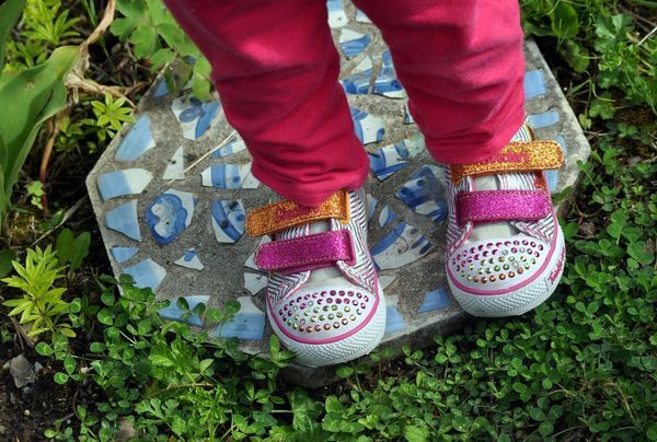 Child's feet standing on homemade stepping stone