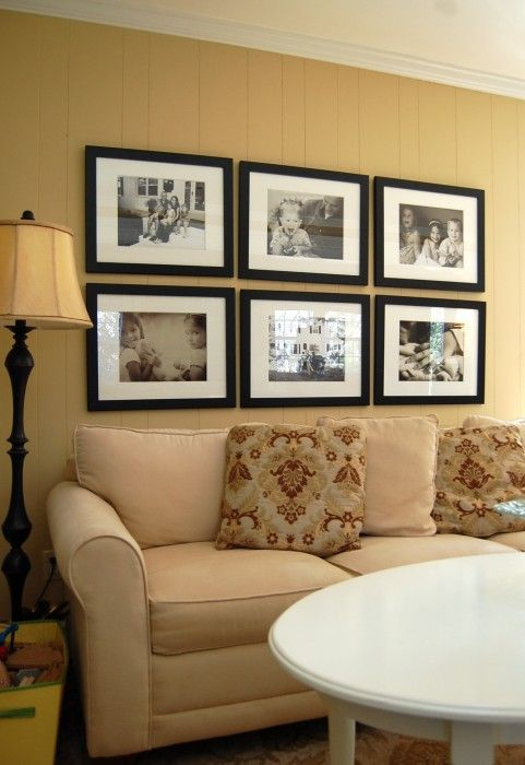 photo wall above couch - colored frames
