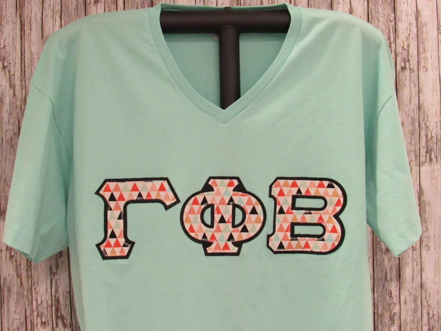 sorority double stitched letters chill light aqua shirt with multi color triangle print