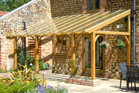 A timber pergola with a glazed roof built as a lean-to on a barn  conversion, with small raised brick planters - A Timber Pergola With A Glazed Roof Built As A Lean-to On A Barn