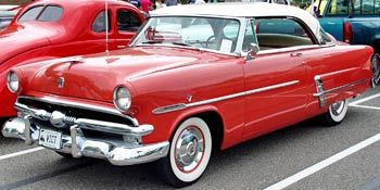 """1953 Ford - Ford celebrated its 50th anniversary in 1953. Only cosmetic updates distinguished the 1953 models from the 1952s. A special steering-wheel-hub medallion announced """"50th Anniversary 1903-1953"""". The grille incorporated a larger horizontal bar with three vertical stripes on either side of the center bullet."""