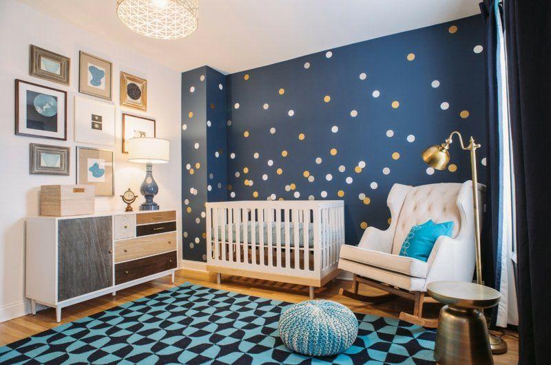 chambre bébé blanche et bleu marine avec tapis, pouf, mur à pois et commode  vintage