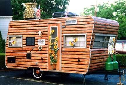 This trailer has been painted to look like a Log Cabin... Check out the sunflowers growing up the door and the chiminey. (I am also pinning the painted hubcaps.) Currently for sale on Craigslist in Cincinnati.