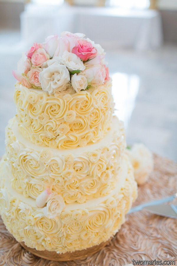 Three tier wedding cake in multiple flavors covered in piped ...