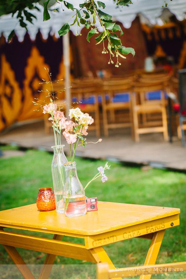 Detail van de bloemen op een houten tafeltje en stoeltje, neergezet ter decoratie en natuurlijk als rustpunt voor de gasten van deze tuinbruiloft.