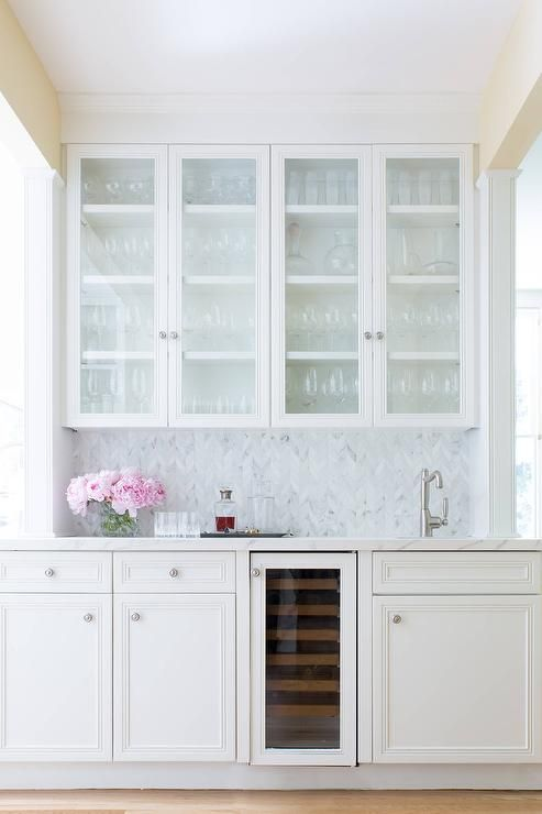 beautiful white wet bar features glass front white cabinets mounted against a marble herringbone backsplash above