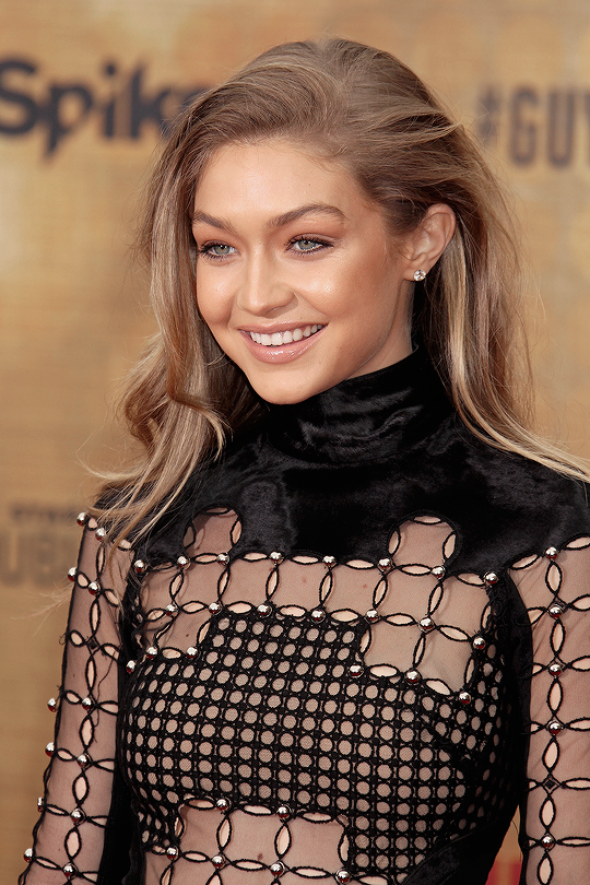 Gigi Hadid with glowing tan and sandy blonde hair - wearing black velvet pattern dress and simple diamond earrings