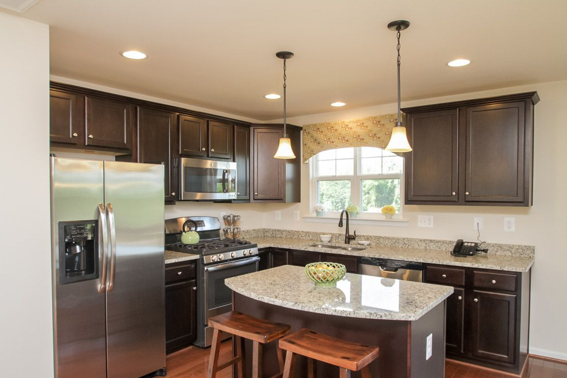 Kitchen with hardwood flooring, espresso cabinets with crown moulding, pendant and recessed ligh ...