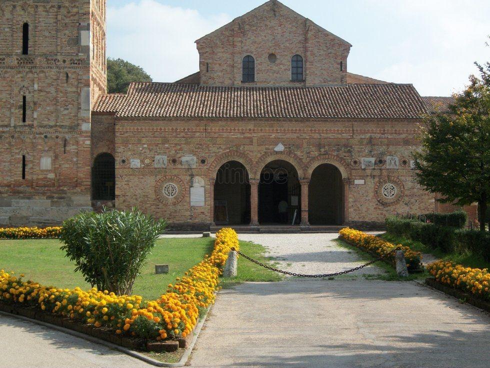 Abadía de Pomposa situada en el municipio de Codigoro, en la provincia de Ferrara, es una abadía del siglo IX. La basílica, de estilo semejante a la de Rávena, fue construida entre los siglos VII y IX; fue luego alargada y se le añadió un pórtico adornado con frisos. Consta de tres naves; las paredes hay frescos del siglo XIV de la escuela boloñesa, y en el ábside, otros debidos a Vitale da Bologna.