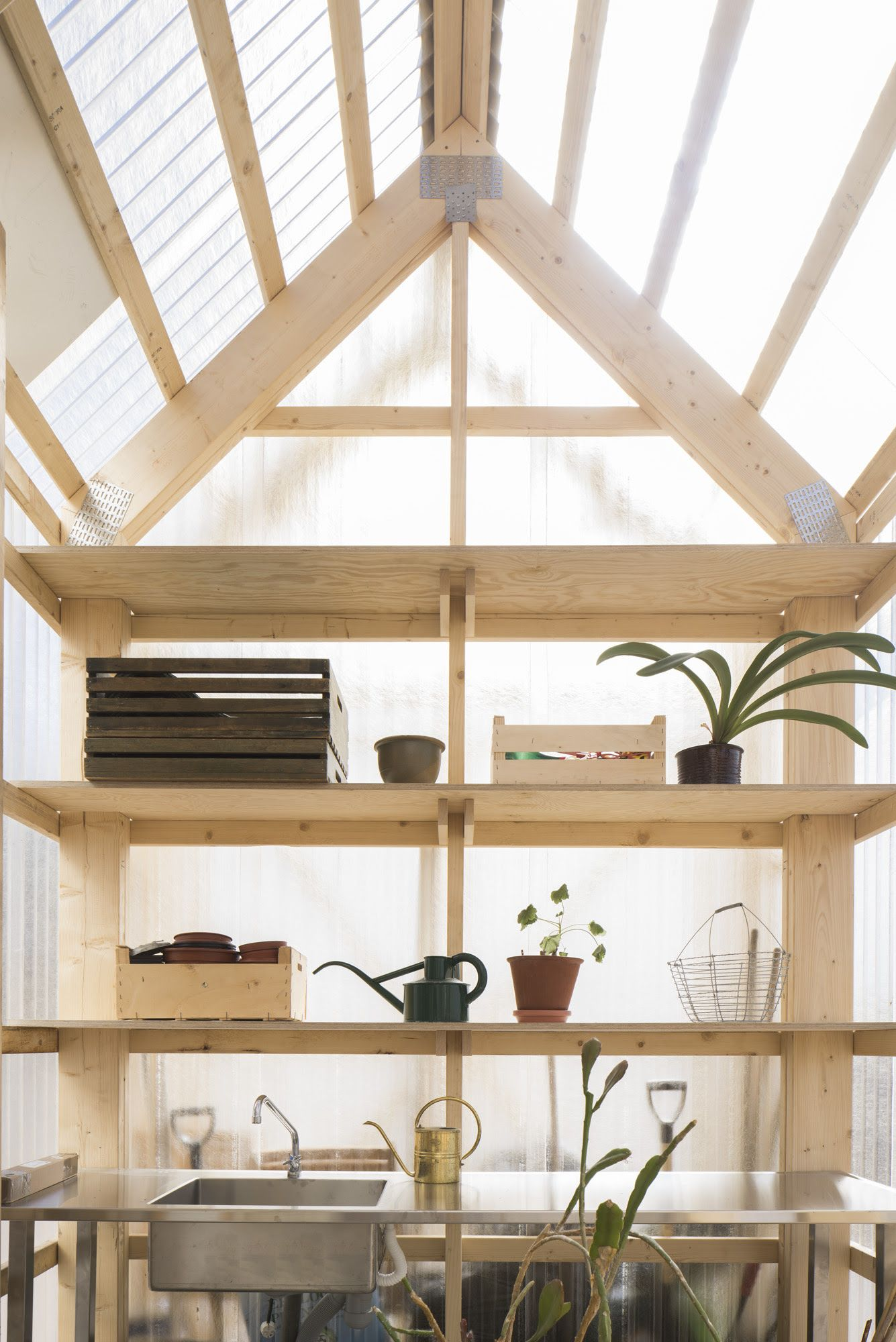 A greenhouse with translucent corrugated polycarbonate walls and exposed wood frame in forstberg lings house for mother