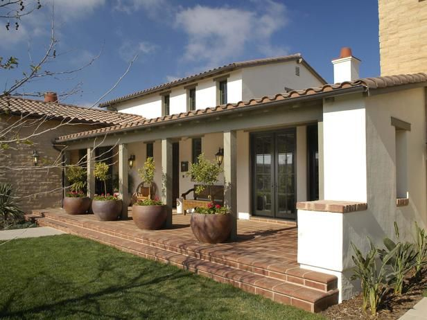 Mission Porch: The signature piece enhancing this exquisite elevation is the expansive front porch complete with large plant containers and stucco. From HGTVRemodels.com