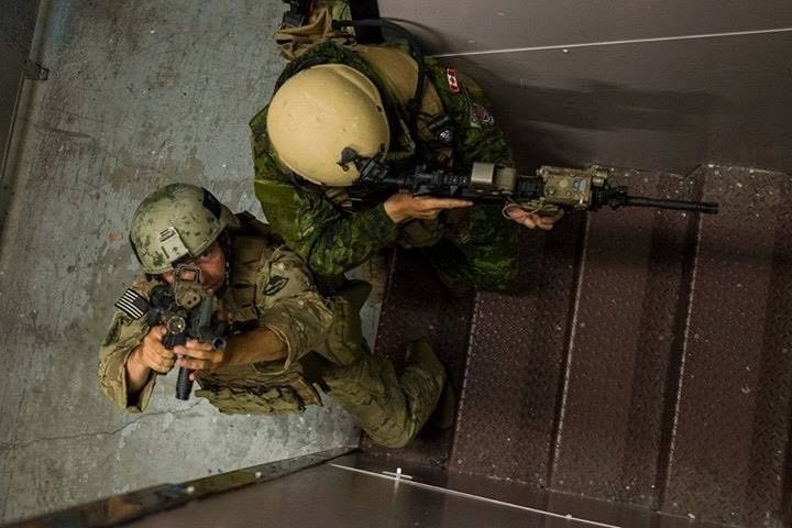 A Usarmy Soldier Assigned To 982nd Combat Camera Company Airborne And A Canadian Forces Soldier Assigned To Canadian Combat Camera Clear A Stairwell D