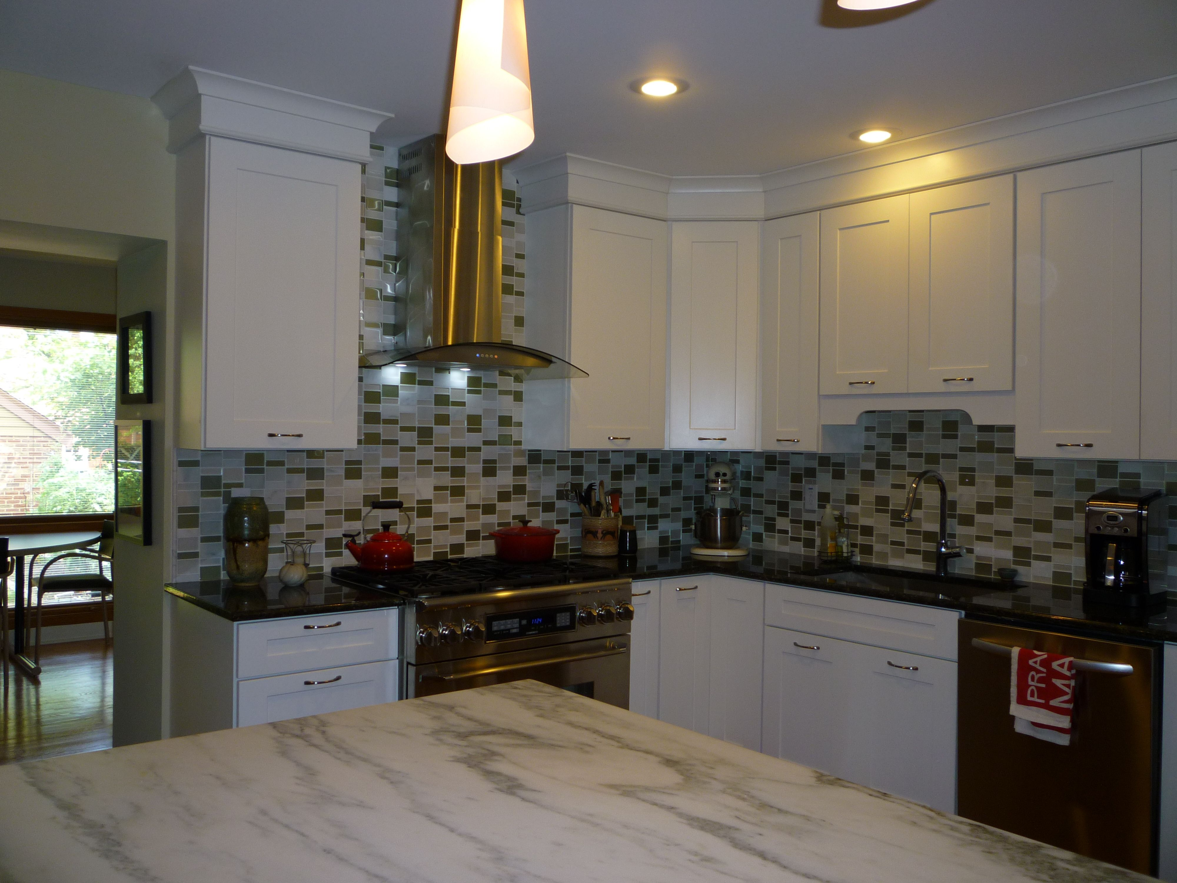 remodeled kitchen white cabinets glass tile black splash granite counter with dark cabinet