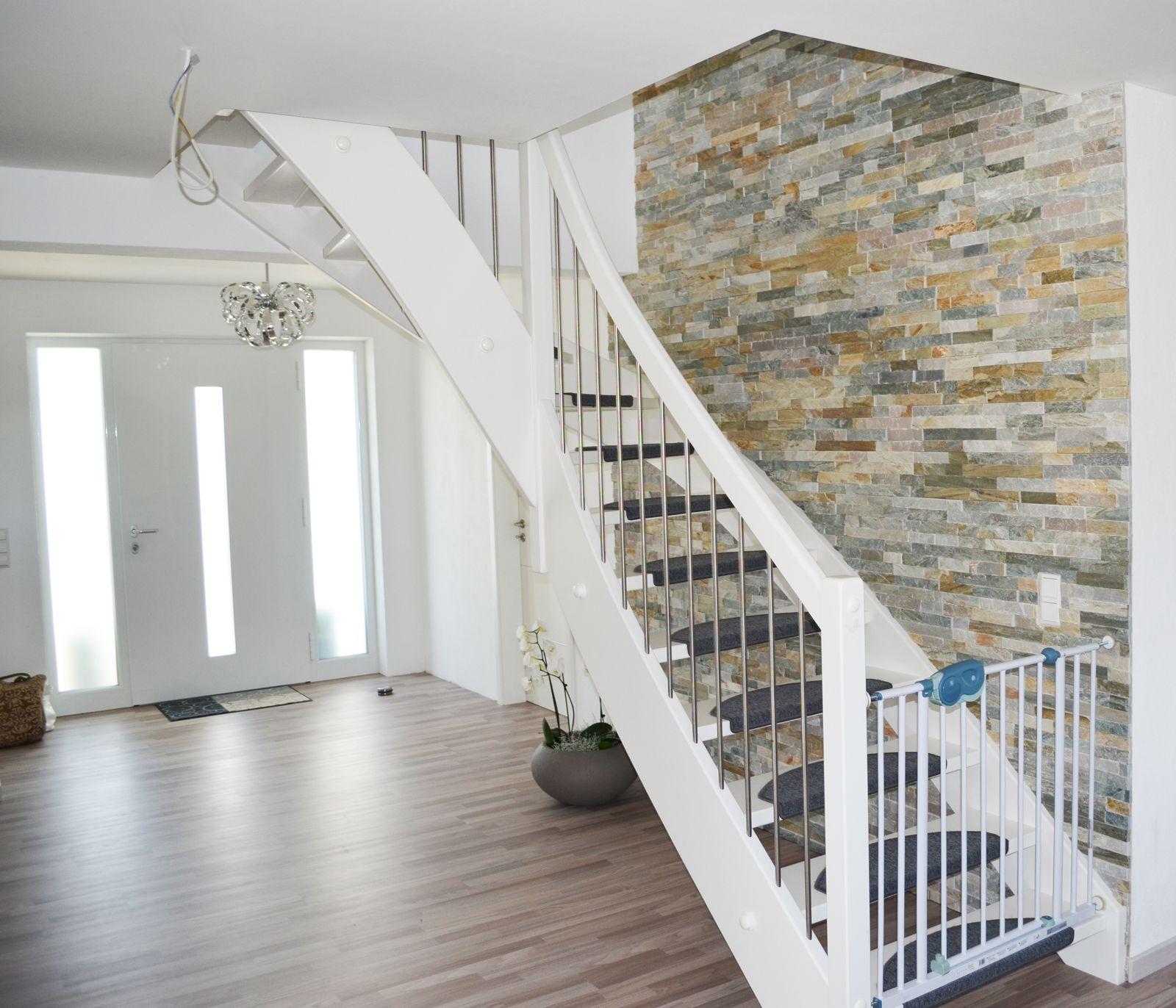 Eine weiße Treppe mit Teppichaufsatz Als Kindersicherheit nt das Türchen am Boden