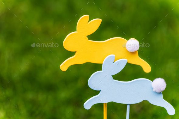 Wooden Bunnies as Symbols of Easter by Manuta Wooden Bunnies as Symbols of Easter on Dark Green Natural Background