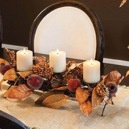 Faux pomegranate and pinecone candleholder with silk leaves and feathers.  Product: CenterpieceConstruction Material...