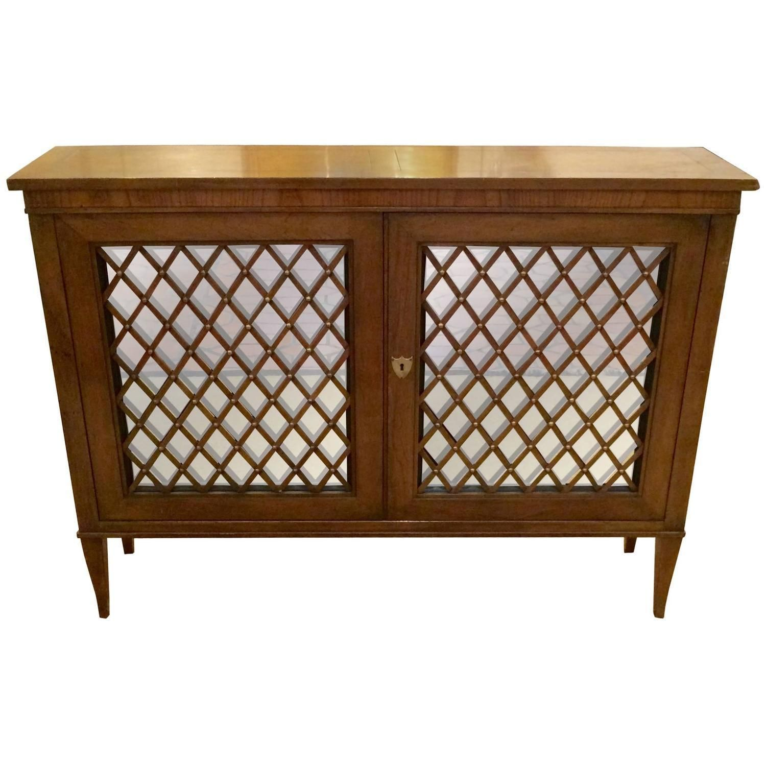 A great looking and versatile walnut credenza cabinet by Baker, having two mirrored doors with decorative wood lattice on the fronts, embellished with brass studs, revealing storage inside. Elegant tapered legs and brass shield key hole. Great in a foyer, hallway, used as a bar, etc. Baker label inside.