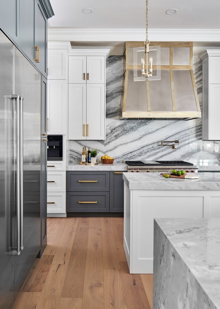 This stunning kitchen with a full height marble backsplash and custom metal rang...