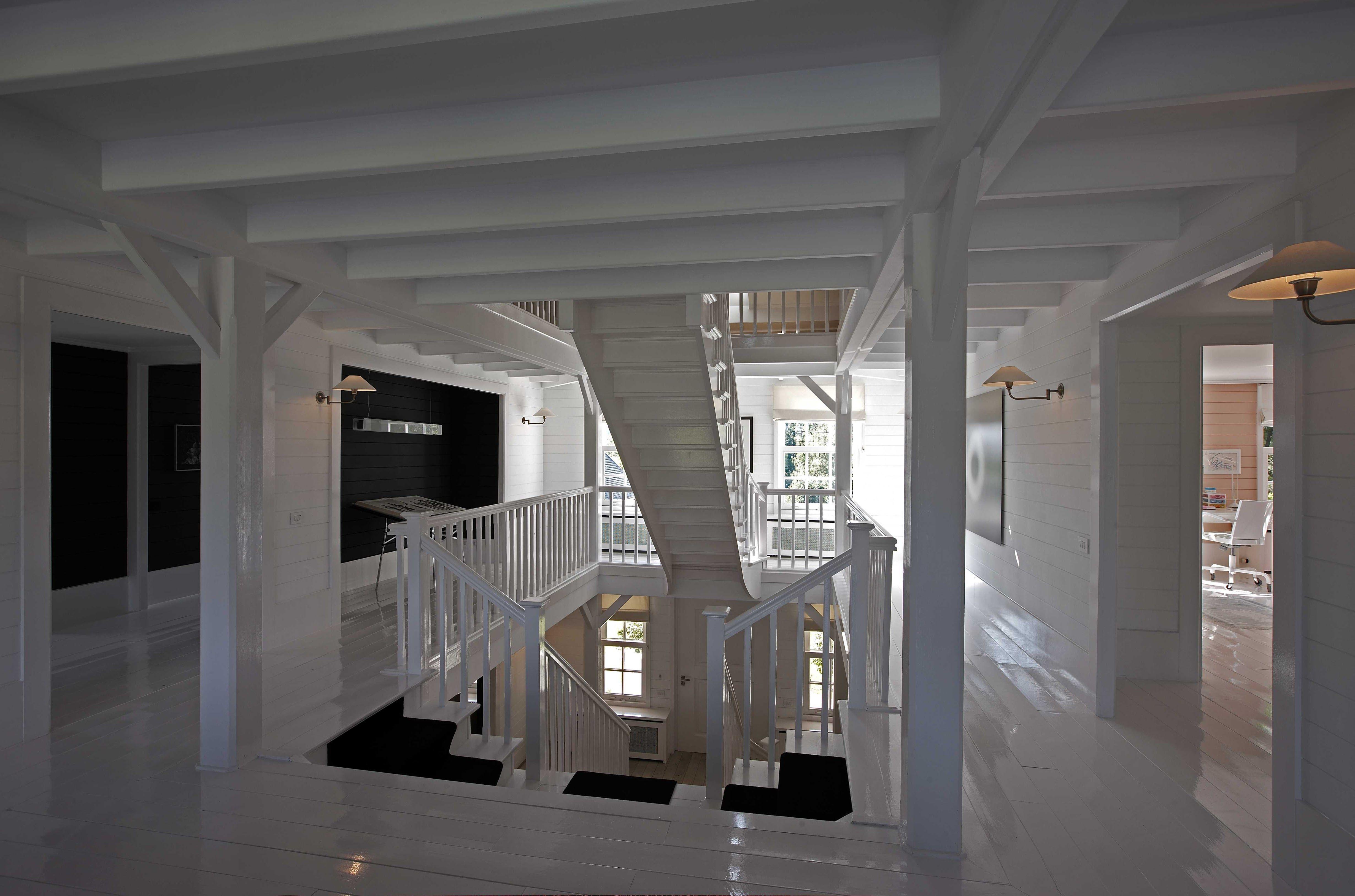 Hal witte trap trappenhuis entree houten vloer wit houten balklaag