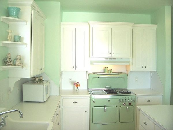 Sweet little kitchen with simple white cabinets and shelves - but thatawesome mint green Chambers stove says it all.