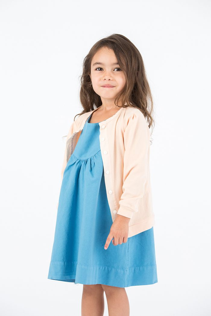 """SS 16: A serene and loving mood pervades Kristin Coia's Go Gently Baby collection of organic cotton separates for girls and boys. T-shirts for boys offer the message, """"No Sleep for Peace,"""" while a palette of subdued shades lend a sense of calm. The Boardwalk Dress's deep curved bodice adds shape and femininity to the simple A-line shape. The Kit Cardigan has a weathered look enhanced by rivershell buttons. www.gogentlybaby.com"""