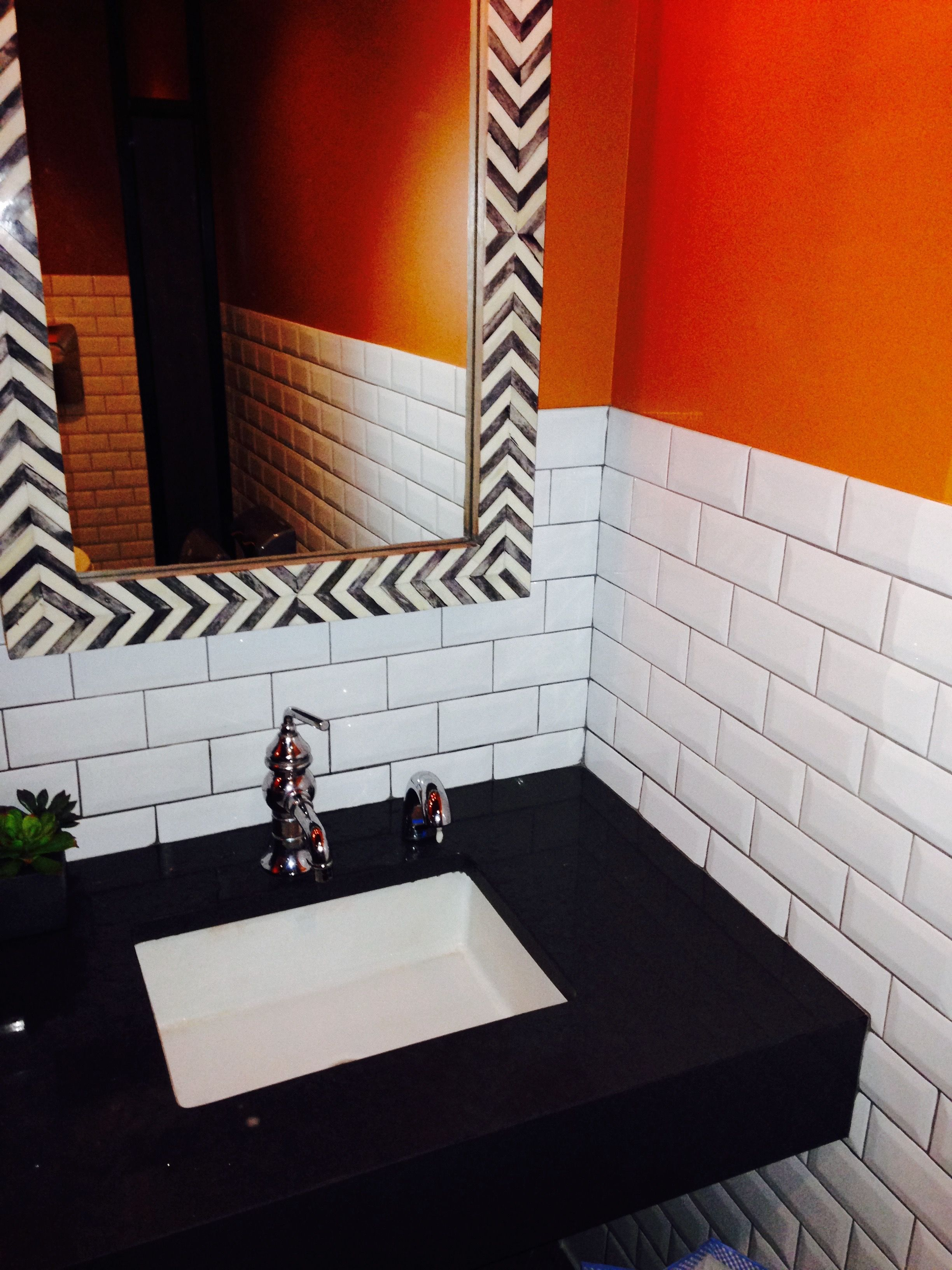 White Subway Tile With Orange Accent Wall And Black Bathroom Counter