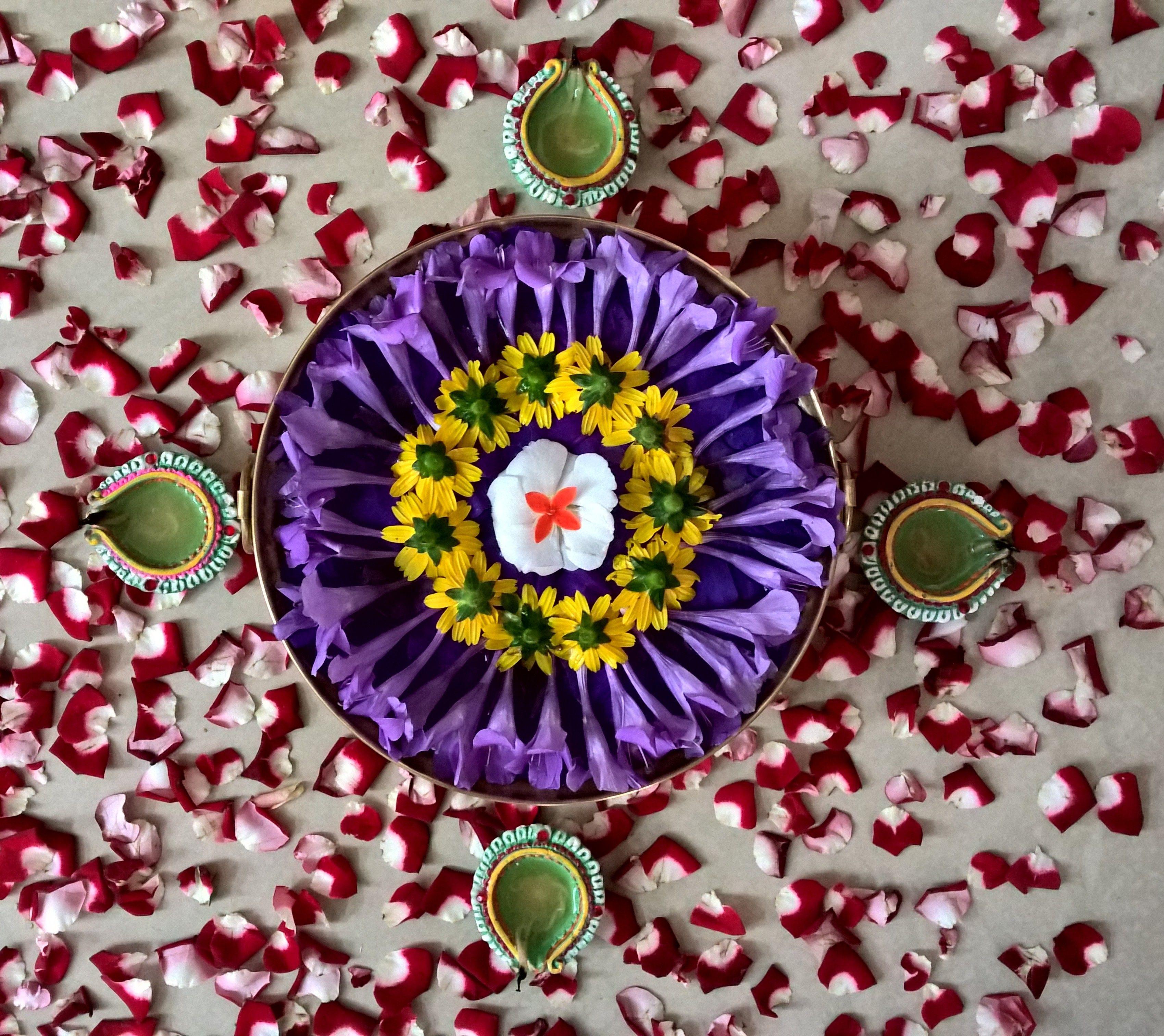 Rose petals arranged around floating flowers.. Flower