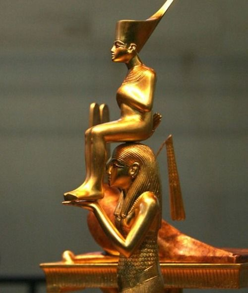 Menkheret Carrying Tutankhamun. Golden statues from ancient Egyptian tomb.