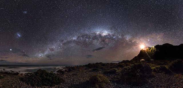 Guiding Light To The Stars. A view of the Milky Way from the North Island in New Zealand. The light on the right is from the Cape Palliser Lighthouse. Credit to Mark Gee.