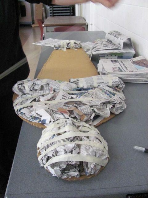 Making a mummy cutting the cardboard to shape, smooshing newspaper - halloween office decorations