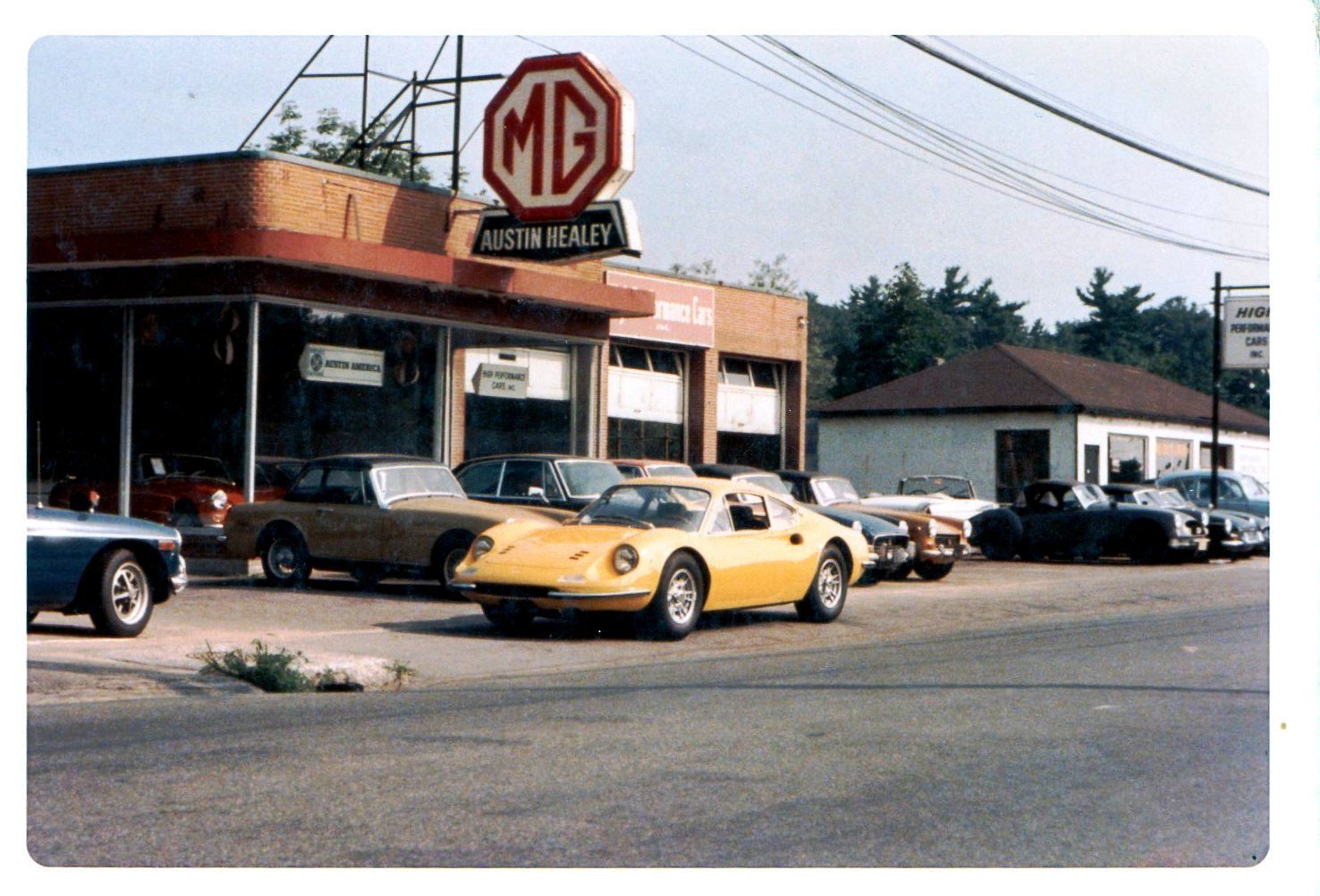 A yellow Dino 206 GT parked in front of an american MG