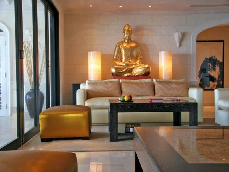 Elegant zen living room with gold buddha statue decor for Small living room zen design