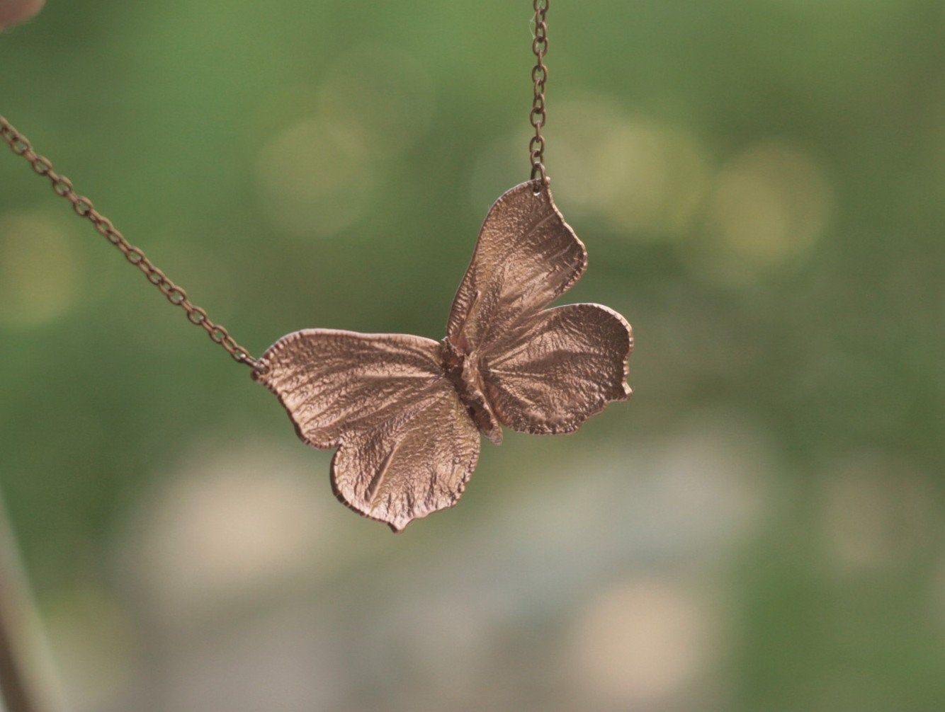 Butterfly necklace, open wings, copper electroplated bug
