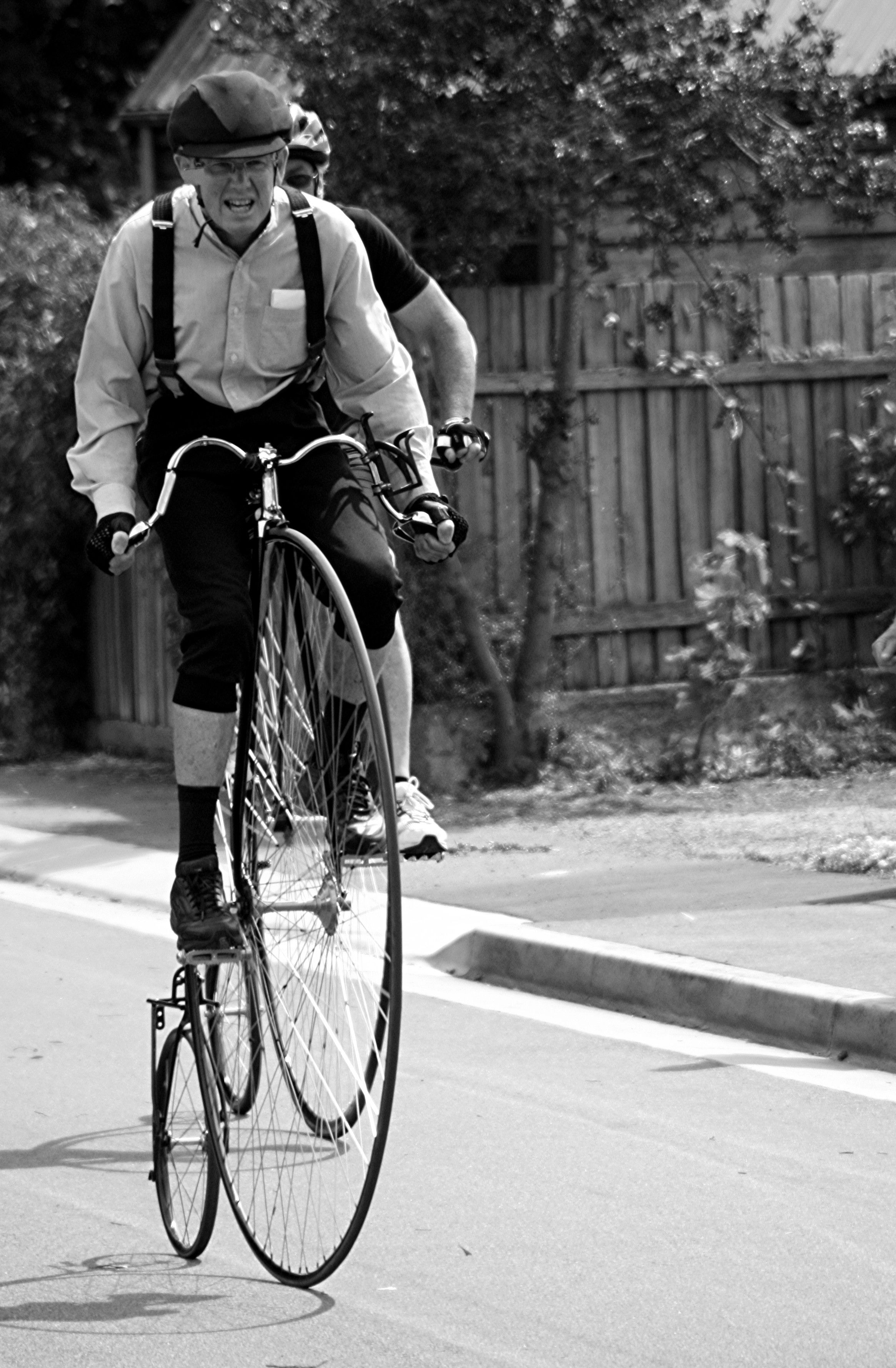Penny farthing bycycle, veteran riding in full costume of