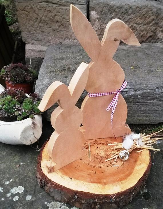 Schöne Osterdekoration bestehend aus zwei Hasen die auf einer Baumscheibe montiert sind. Die Hasen und die Baumscheibe sind unbehandelt und können nach belieben selbst weiter gestaltet und/oder dekoriert werden. ( Moos, Eier usw.) Der große Hase ist ca. 36 cm hoch und der kleine ca. 25