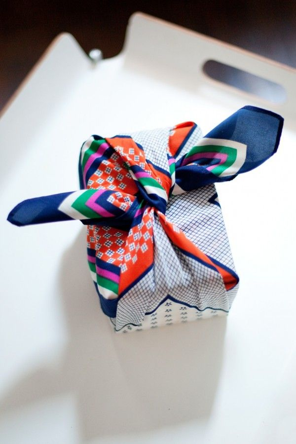 a scarf acts as functional wrapping paper and a bonus gift for the recipient. a win-win.