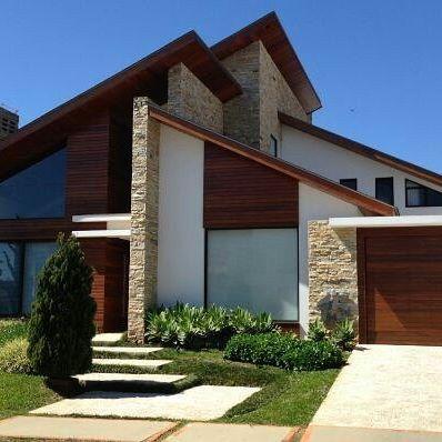 Casa com detalhes em pedra com madeira e telhados jardim for Casas contemporaneas rusticas