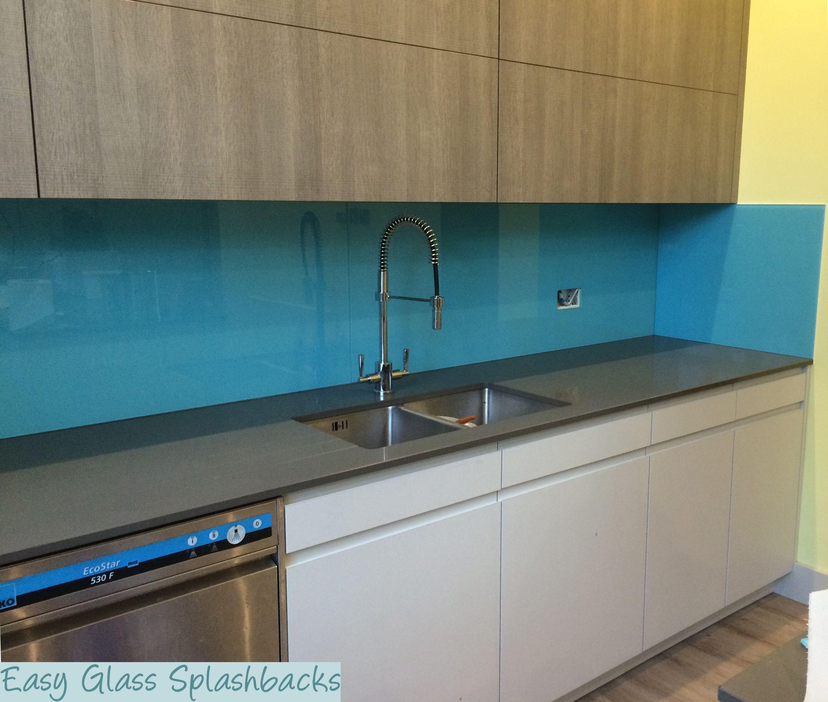 Light Sky Blue Coloured Glass Splashback In A White Kitchen With Black Worktop Visit Easyglasssplashbackscouk To Discover More