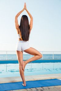 back view portrait of a girl standing in yoga pose on one