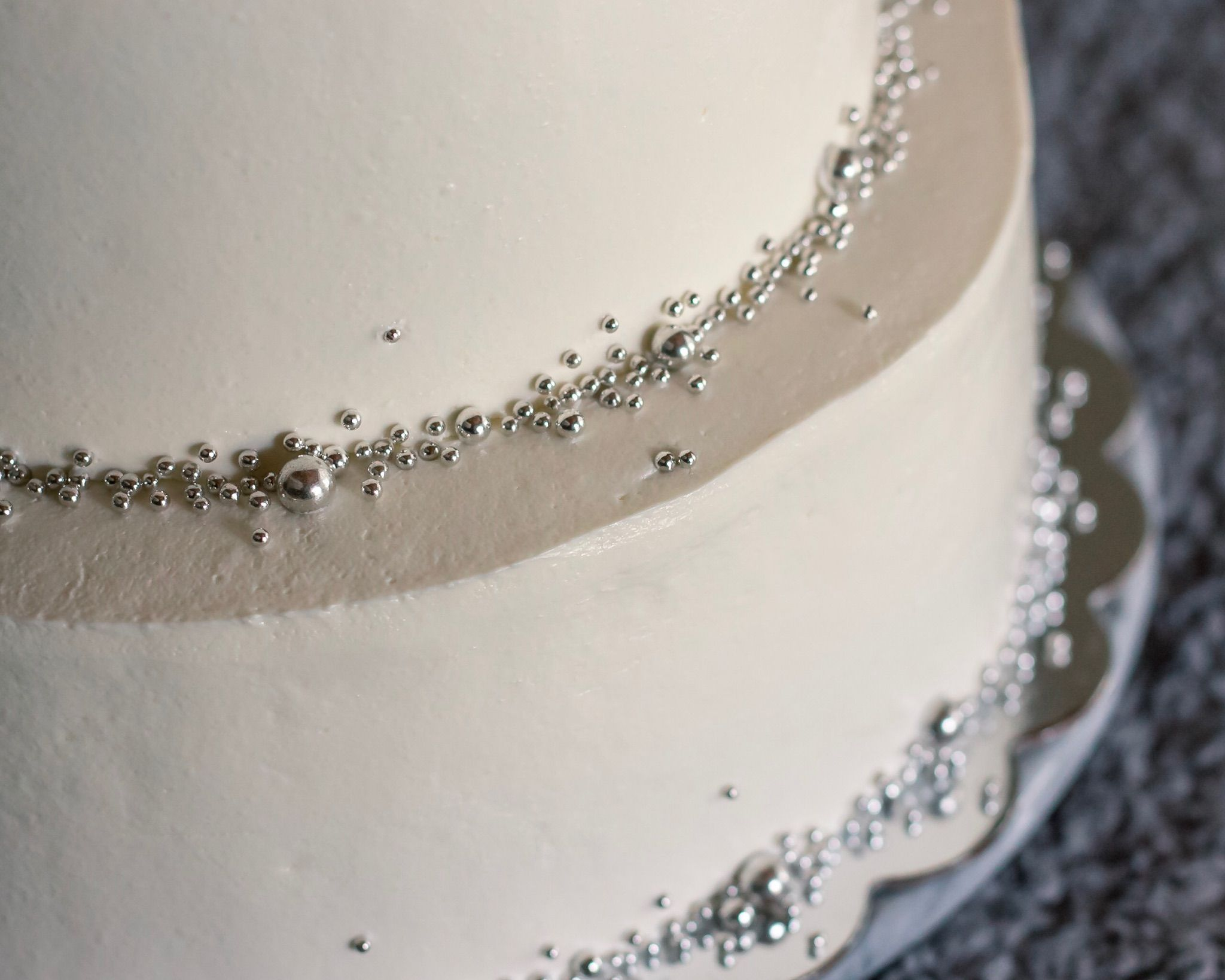 Silver beaded detail on a white wedding cake simple and elegant