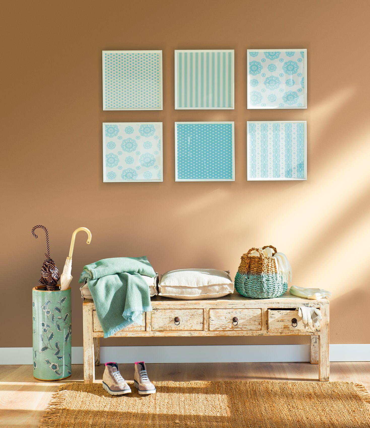 Recibidor con paragüero, banco de madera y cuadros en tonos azules y ...