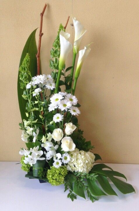 Contemporary funeral arrangement. White and green with calla lilies, daisies, roses, dendrobium orchids, bells of ireland and hydrangeas.