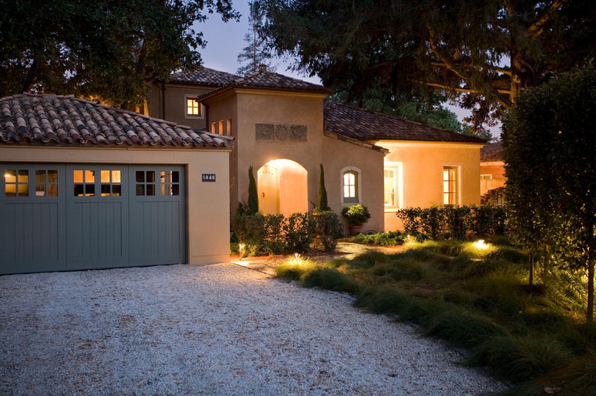 Stucco exterior gravel driveway terracotta roof blue garage door