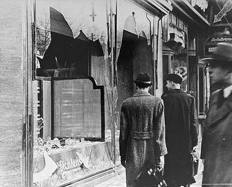 Kristallnacht.  Germans pass broken window of Jewish-owned shop (USHMM Photo)