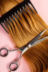 Top view of scissors and comb on brown hair on pink background