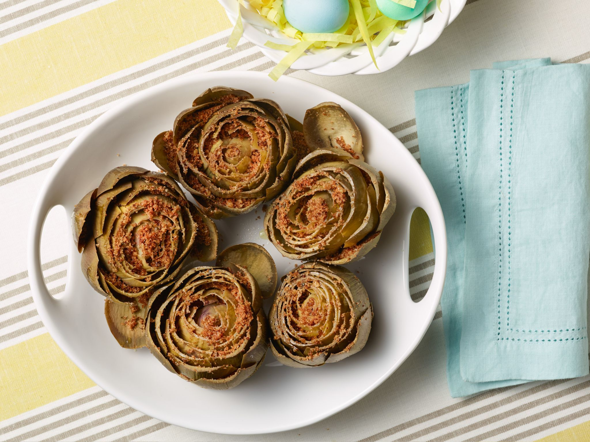 Slow-Cooker Braised Artichokes with Toasted Garlic Breadcrumbs : Add these easy-to-make stuffed artichokes to your Easter dinner menu and watch how quickly they disappear. Your guests will love peeling off the tender leaves, and they'll be happily surprised to find little pockets of garlicky breadcrumbs inside. For a spicy kick, add a pinch of crushed red chile flakes to the breadcrumbs.