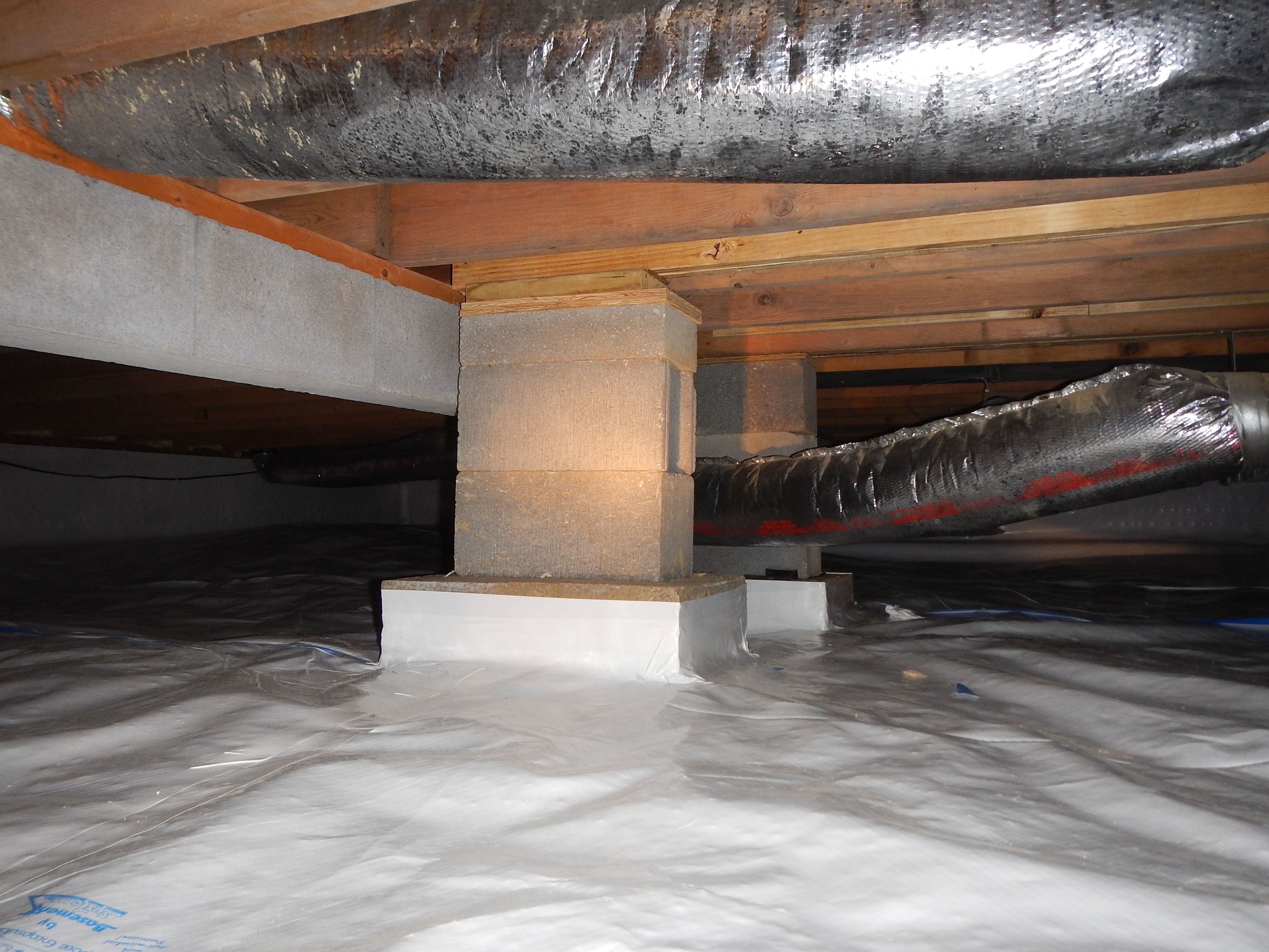 Crawlspace block piers added to a beam between the floor Concrete crawl space floor