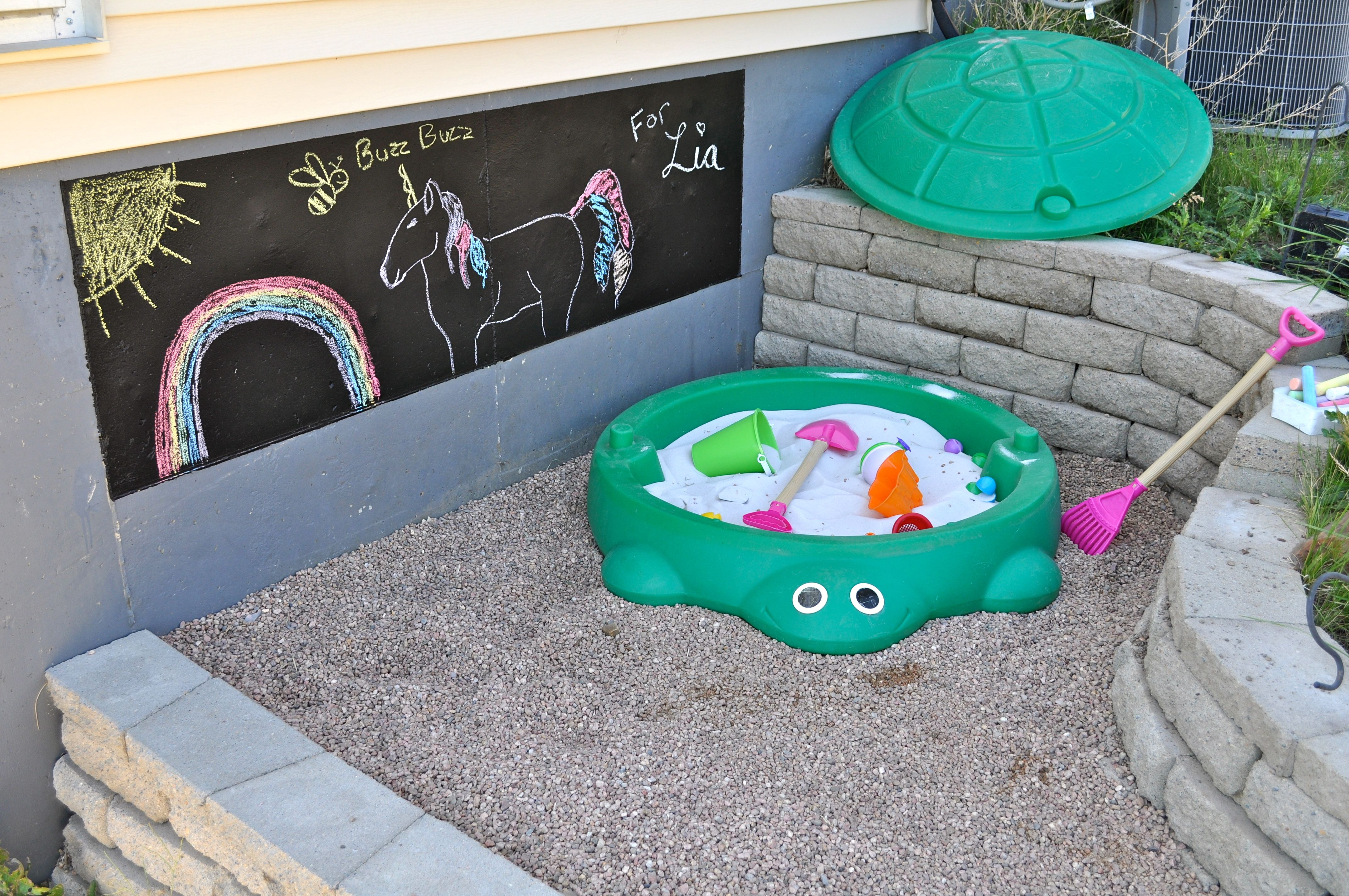 Aurelia's Nook! ~this is a retaining wall area on the side of our house that Rich entirely built. It is shady most of the day, and it was the perfect place to put the sand box! My idea was the chalk board paint on the foundation so that she can make art! A great space for a kid! :-)